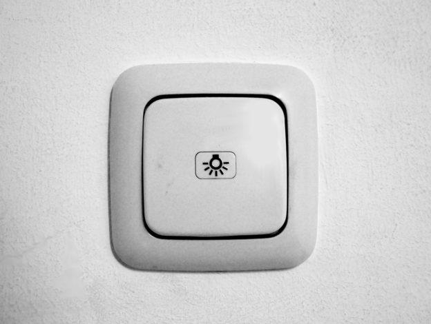 An einer weißen Wand sieht man einen weißen, einfach Lichtschalter, der ein Glühlampen-Symbol mittig aufgebracht trägt.