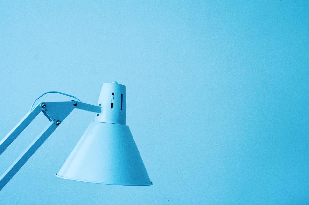 Ein hellblauer Lampenschirm einer Schreibtischlampe für Kinder vor hellblauem Hintergrund