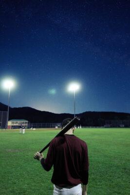 Ein Mann hält einen Baseballschläger. Das Feld um ihn Herum wird von Flutlicht erhellt.