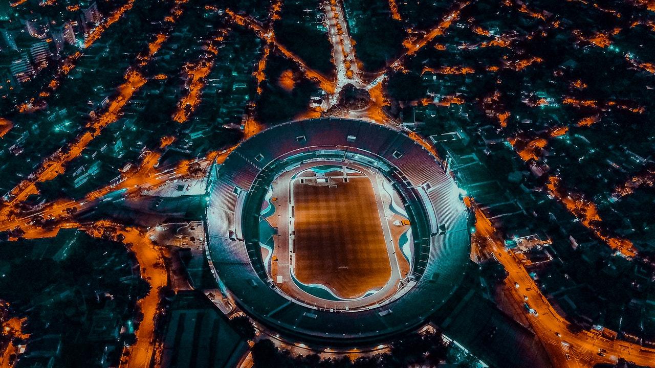 Aus der Vogelperspektive wird der Blick auf ein bei Nacht in Flutlicht erleuchtetes Stadion gerichtet.