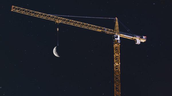Ein Kran wird nachts beleuchtet. Im Hintergrund sieht man den Mond