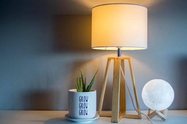 Eine Tischleuchte steht auf einer Holzoberfläche. Sie strahlt warmes Licht ab. Neben ihr steht ein kleiner Blumentopf mit Grünpflanze darin.