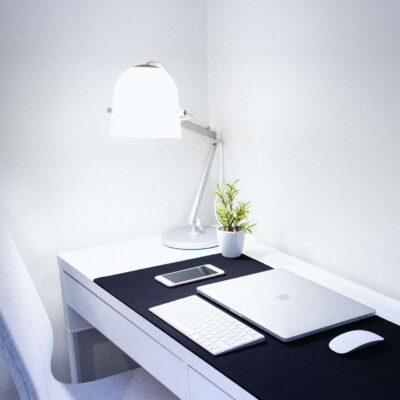 Auf einem Schreibtisch steht eine weiße Schreibtischlampe, die alles in sehr kühles Tageslicht taucht. Neben ihr steht eine kleine Topfpflanze.