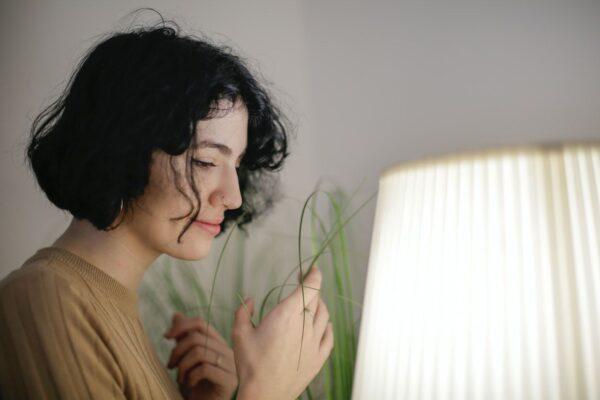 Eine Frau steht vor einer großen Leuchte mit Lampenschirm, neben ihr steht ein hoch gewachsenes Gras, dessen Halme sie teilweise in den Händen hält.