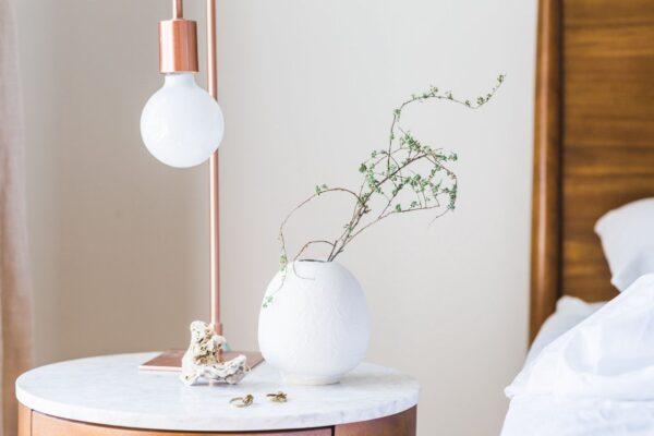 Eine kupferfarbene Tischlampe steht neben einer weißen Vase, in der einige grüne Zweige stehen.