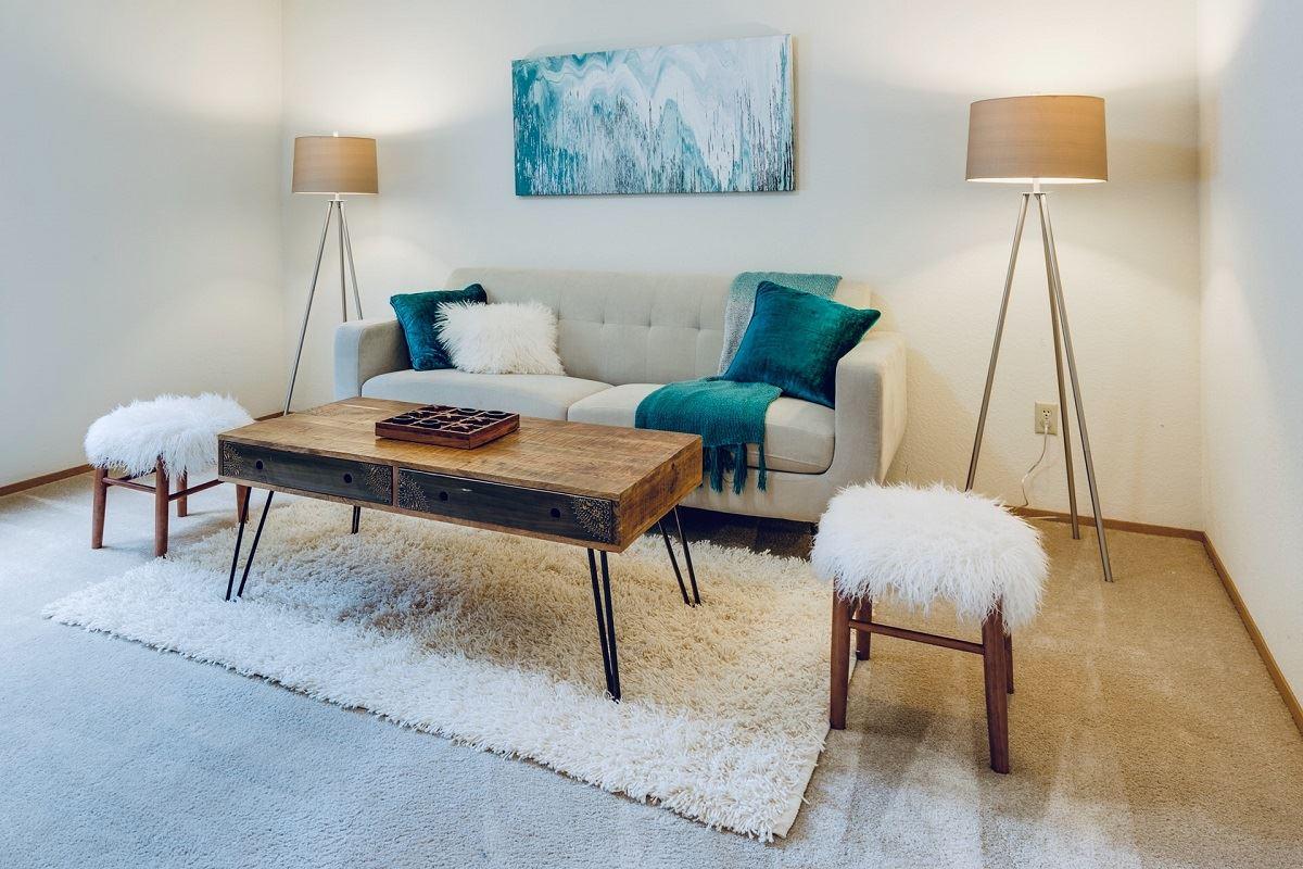 Minimalistisch eingerichtetes Wohnzimmer mit einem Sofa und zwei Tripod-Stehlampen