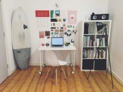 In einem kleinen Raum mit weißen Wänden und hellen Holzdielen steht ein Schreibtisch mit Stuhl und Regal, zu dessen Linken lehnt ein Surfbrett an der Wand, zur Rechten steht eine Tripod-Stehleuchte