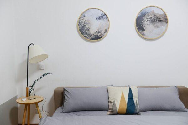 Eine Tripod-Stehleuchte aus hellem Holz mit integriertem Nachttisch und einem cremefarbenen Lampenschirm steht neben einem Bett.