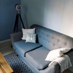 Graues Sofa mit einer dreibeinigen Leuchte im Steampunk-Stil dahinter