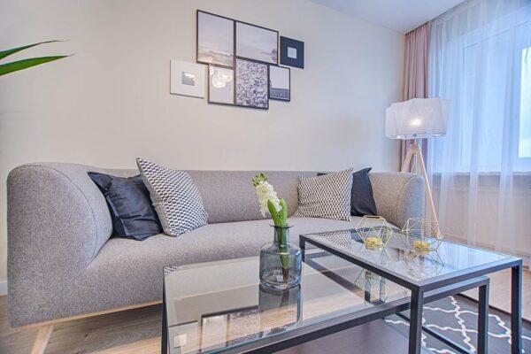 Modern eingerichtetes Wohnzimmer in hellen Farben mit dunklen Metall-Kontrasten und cremefarbener Tripod-Stehlampe mit geometrisch-gefalteten Lampenschirm