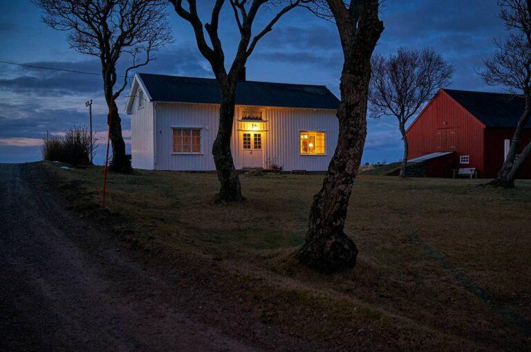 Ein innen und außen beleuchtetes Gartenhäuschen am Abend