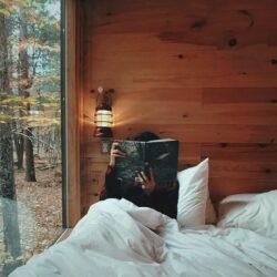 Jemand ließt ein Buch im Bett eines Gartenhauses mithilfe einer kleinen Wandleuchte.