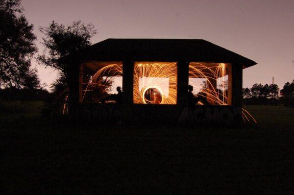 Bei Nacht experimentieren Menschen in einem Gartenhaus mit der Fotografie von Lichteffekten.