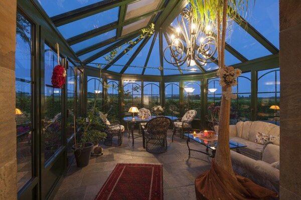 In einem gemütlich eingerichteten Wintergarten strahlt von der Decke ein Kronleuchter.