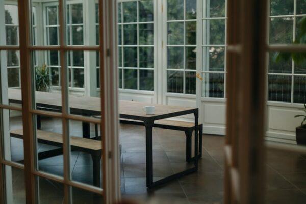 Aus dem Inneren des Hauses geht der Blick in einen Wintergarten mit großem Esstisch in der Mitte hinaus.