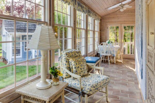 Ein Wintergarten aus Holz ist mit verschiedenen Tischen und Stühlen gemütlich eingerichtet.