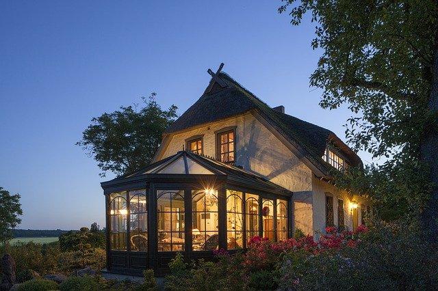 In der Dämmerung sieht man ein Haus mit eingeschalteter Wintrgarten-Beleuchtung.