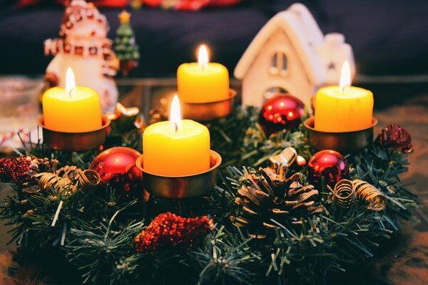 Auf einem mit Kugeln und Tannenzapfen geschmückten Adventskranz brennen alle vier Kerzen.