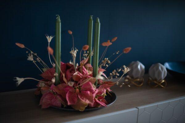 Ein moderner Adventskranz mit vier schmalen, grünen Kerzen und roten Blüten