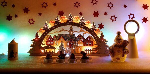 Vor einer mit Sternen dekorierten Wand steht ein erleuchteter Schwibbogen aus Holz mit einem winterlichen Dorf als Motiv.