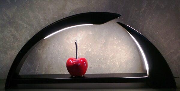 Ein moderner Schwibbogen aus dunklem Holz mit eingelassenen LEDs erhellt eine rote Kirsche als Motiv.
