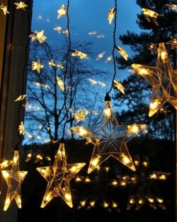 Eine Lichterkette mit Sternen hängt vor einem Fenster