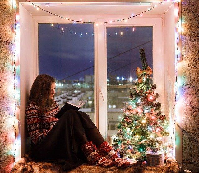 Eine junge Frau sitzt lesend auf einem Fensterbrett, welches mit vielen bunten Weihnachtslichtern geschmückt ist.