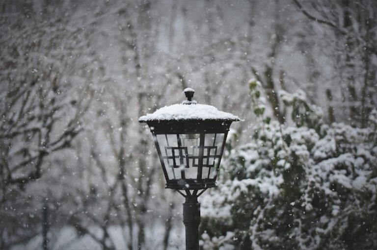 Eine schwarze Laterne steht in einem Garten und ist umgeben von Schnee