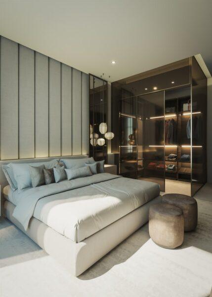 Hinter einem Bett befindet sich ein begehbarer Kleiderschrank mit Beleuchtung