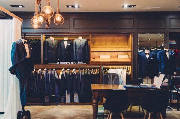 Ein Einbauschrank aus braunem Holz ist innen beleuchtet, in ihm hängen diverse Anzüge.